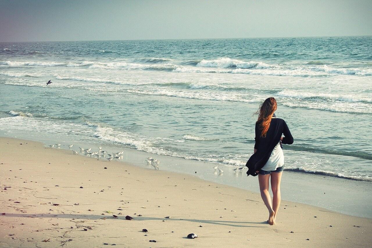 Frau geht entspannt am Strand